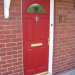 Poppy red entrance door on brick house